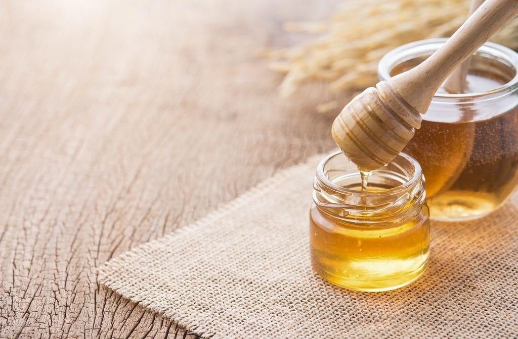 Honig mit hölzernem Honigschöpflöffel auf Holztisch