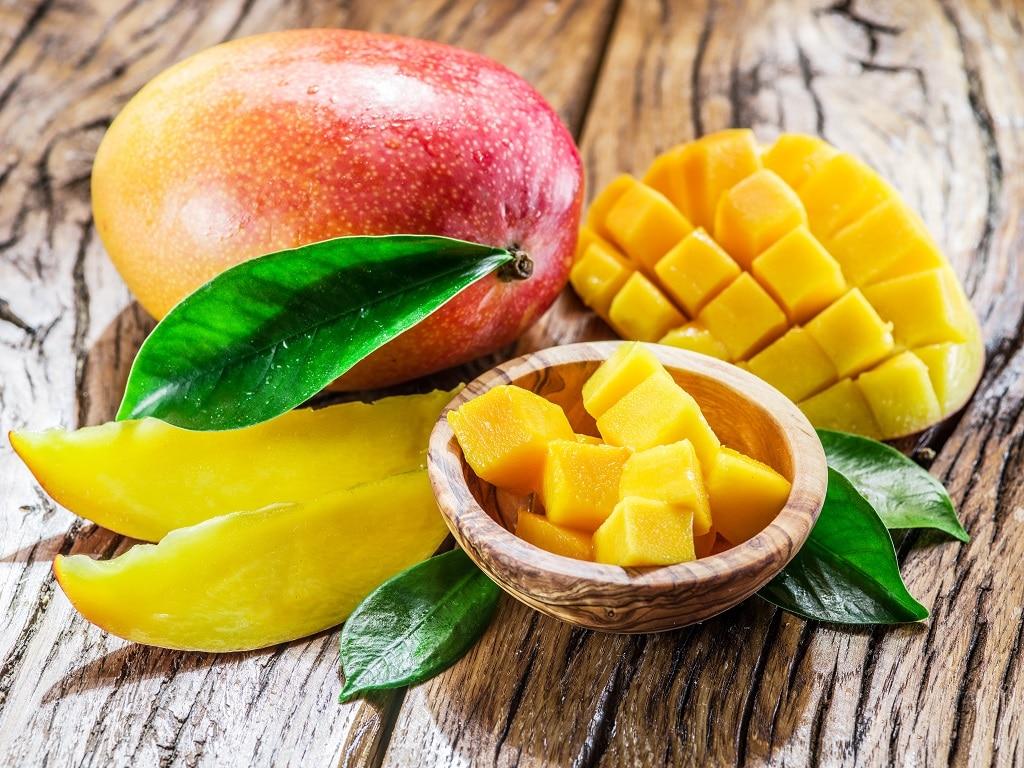 Mangofrucht und Mangowürfel auf dem Holztisch.